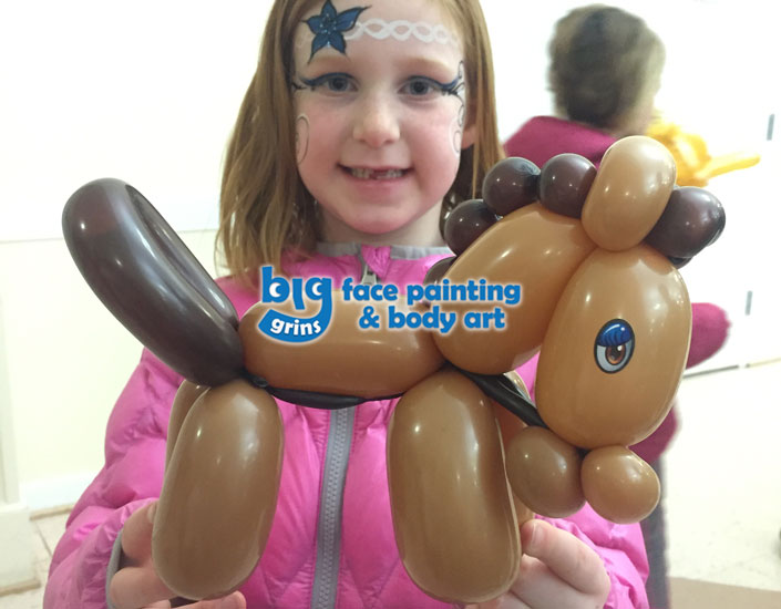 girl holding balloon twisting horse, she is face painted with flower headband