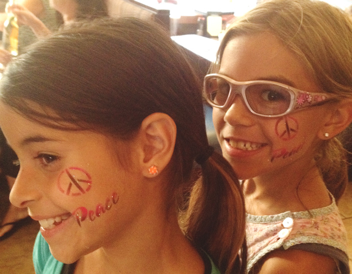airbrush face painted girls with peace symbols
