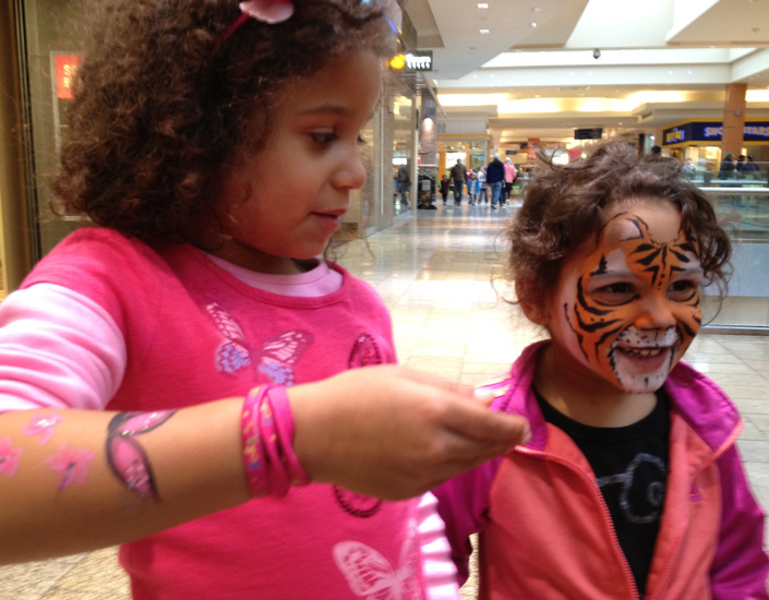 girls showing off their face painting of butterfly and tiger